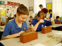 Abergavenny school children carving images of barley in clay bricks that will be included in the sculptures