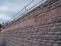 Text by Menna Elfyn and the local community is engraved in industrial-style lettering, built into the retaining walls